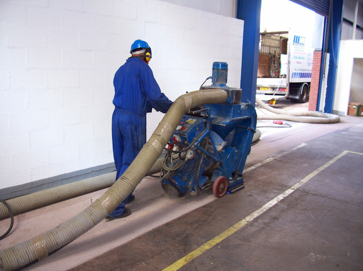 removal of surface coating on warehouse floor by captive shot blasting